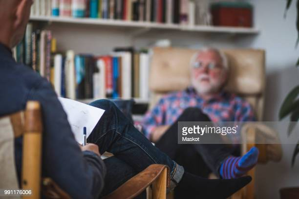 male therapist with senior patient during therapy session - psychologist stock photos and pictures