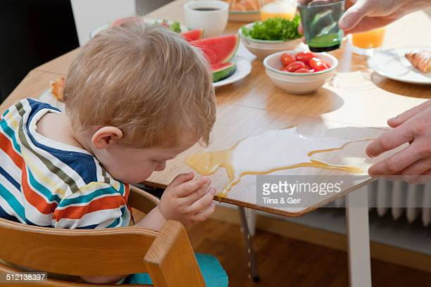 male toddler accidently spilling orange juice at breakfast table - spilling stock pictures, royalty-free photos & images