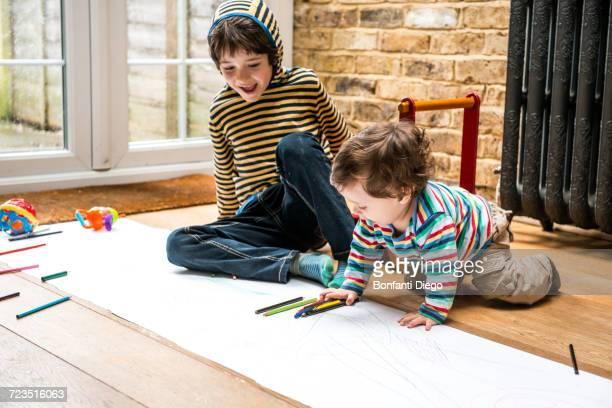 Male toddler and big brother sitting on floor drawing on long paper