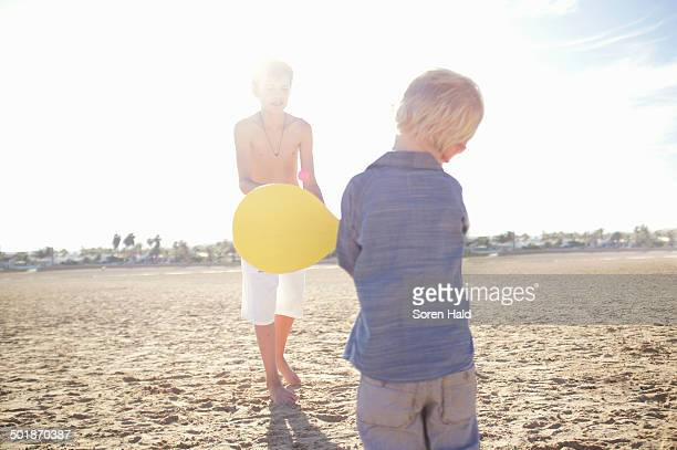 Male toddler and brother playing bat and ball on beach