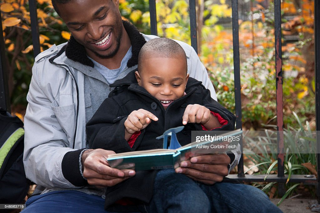 Male toddler and father reading storybook in park : Stock Photo