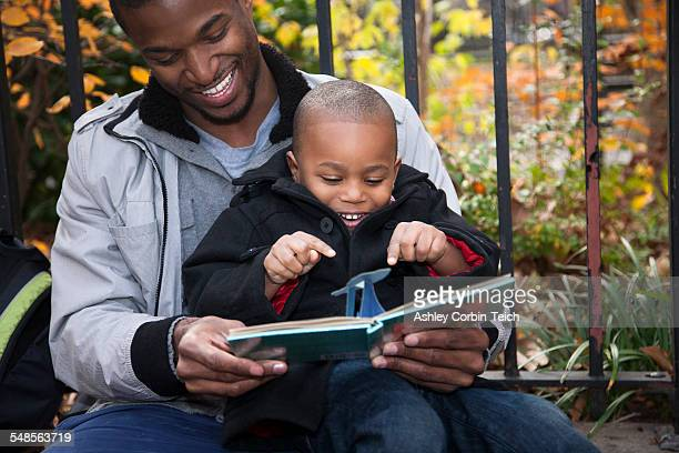 Male toddler and father reading storybook in park