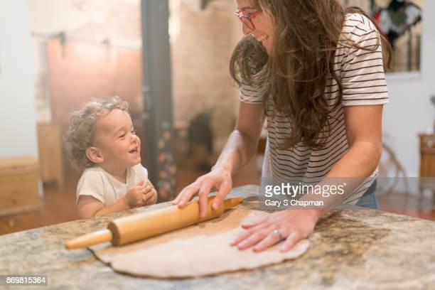 Male toddler and home make homemade pizza.