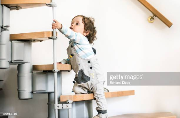 Male toddler climbing stairs