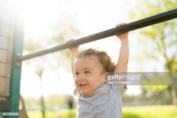 Male toddler exercising on a playground pullup bar.