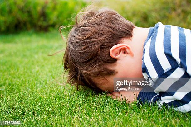 Male toddler hiding face down on grass