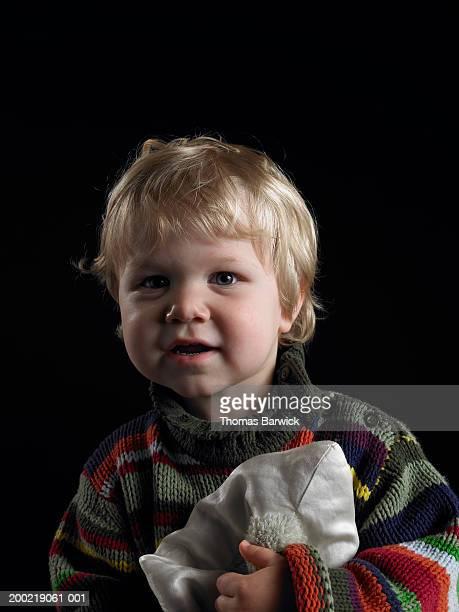 Male toddler (21-24 months) holding blanket, portrait