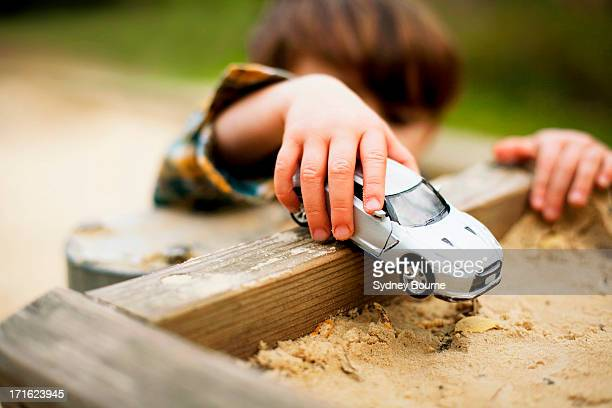 Male toddler holding toy car above sandpit
