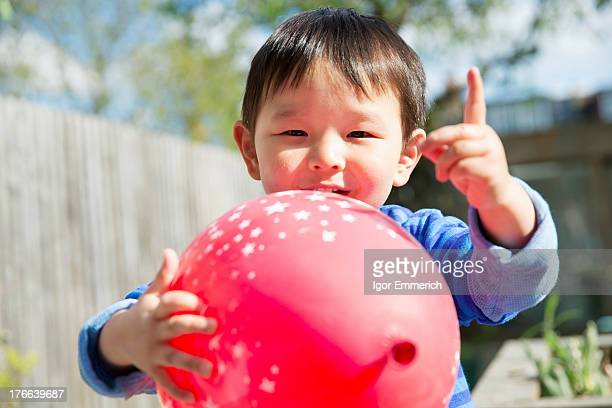Male toddler in garden with red balloon