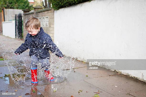 Male toddler in red rubber boots splashing in sidewalk puddle