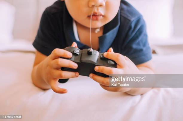 a male toddler is playing with a remote control on the bed - remote controlled car stock pictures, royalty-free photos & images