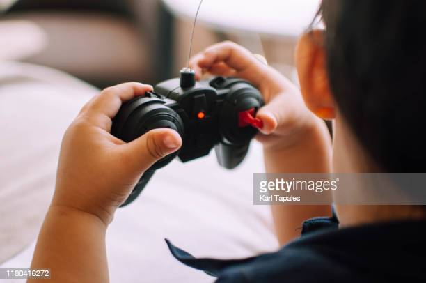 a male toddler is playing with a remote controlled car in the bedroom - remote controlled car stock pictures, royalty-free photos & images