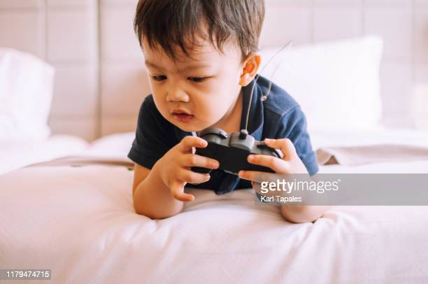 a male toddler is playing with a remote controlled car while lying on front on the bed - remote controlled car stock pictures, royalty-free photos & images