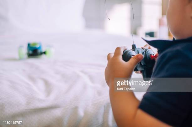a male toddler is playing with his remote controlled car indoors - remote controlled car stock pictures, royalty-free photos & images