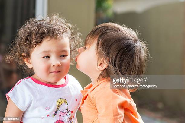 Male toddler kissing female toddler on cheek in back yard