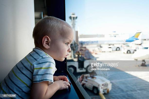male toddler looking out of window at los angeles airport - toddler at airport stock pictures, royalty-free photos & images