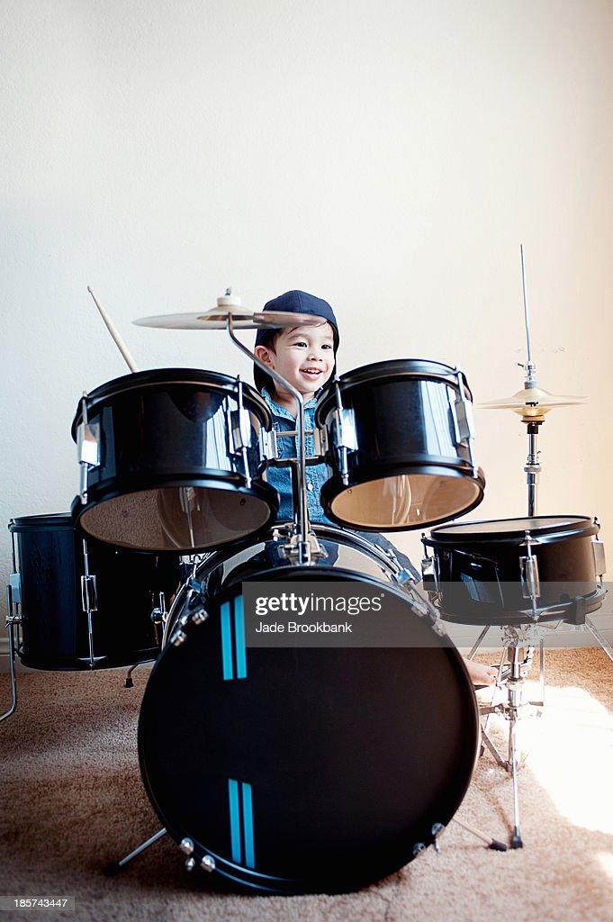 Male toddler playing on drum kit : Stock Photo