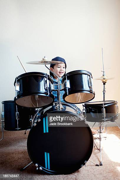 Male toddler playing on drum kit