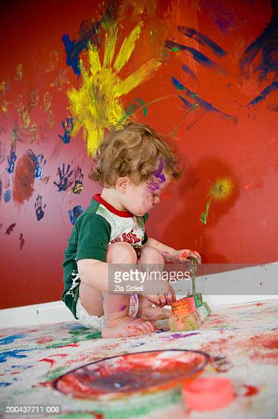 Male toddler (12-15 months) playing with paints