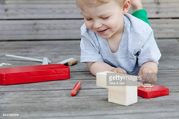 Male toddler playing with wooden blocks for toy boat on pier