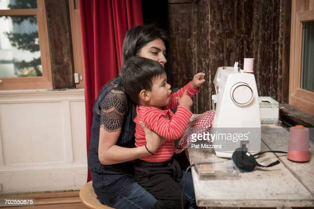 male toddler sitting on mothers lap at sewing machine - mom sits on sons lap stock pictures, royalty-free photos & images