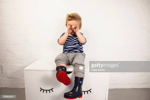 male toddler sitting on toy chest and rubbing his eyes - tantrum stock photos and pictures