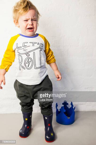 Male toddler standing next to toy crown crying