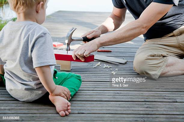 male toddler watching father make toy boat on pier - man made structure stock pictures, royalty-free photos & images