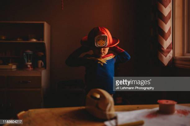 male toddler wears pajamas and a fire helmet in a window lit portrait at home - firefighter stock pictures, royalty-free photos & images
