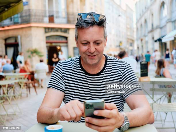 male tourist drinking coffee and using mobile phone outside a cafe - france stock pictures, royalty-free photos & images