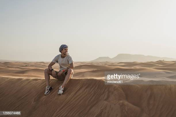 male tourist looking away while sitting on sand dunes in desert at dubai, united arab emirates - desert stock pictures, royalty-free photos & images