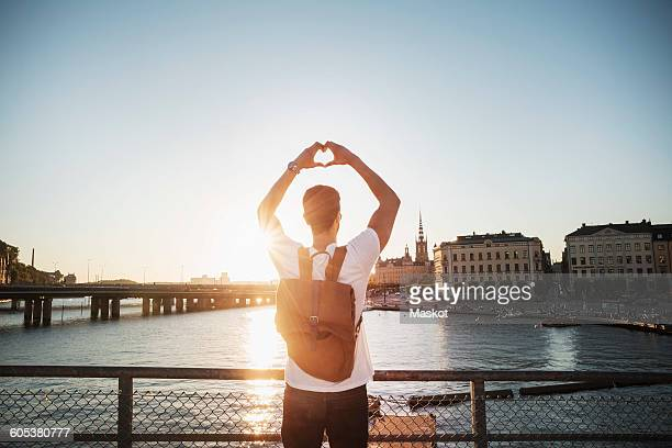 Male tourist making heart shape with hands in city against clear sky