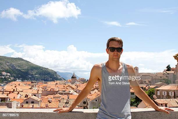 Male tourist poses for portrait on city walls
