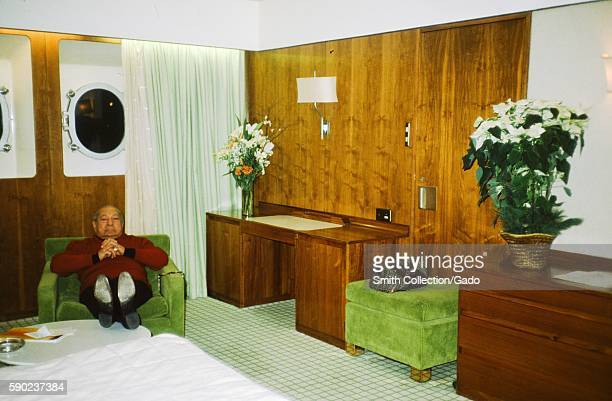 Male tourist sits in a chair with his feet up in a stateroom aboard the Cunard Line's Queen Elizabeth 2 cruise ship at sea 1975