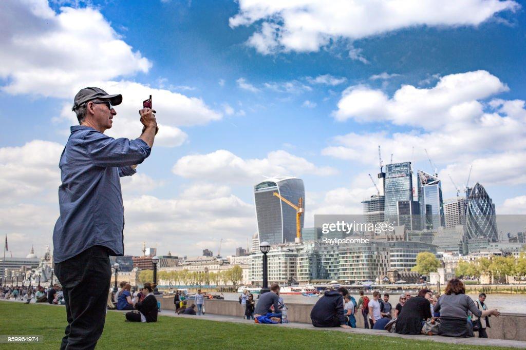 Männlichen Touristen, ein Bild von der Skyline von London in der Londoner Riverside Gegend in der Nähe von Potters Fields Park mit der berühmten Walkie-Talkie, aufbauend auf den Horizont : Stock-Foto
