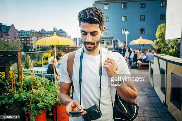 Male tourist using smart phone in city