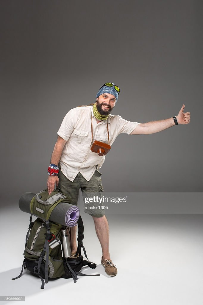 Male tourist with backpack hitchhiking on gray background : Stock Photo
