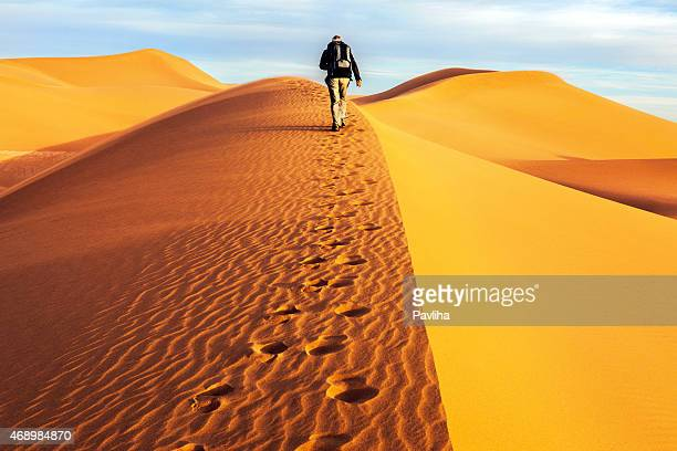 Male tourists walking on the sand dunes, morning, Mhamid, Morocco