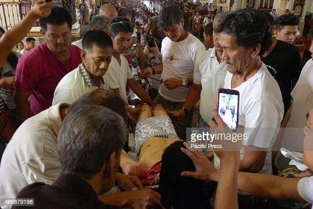 CHURCH MALABON PHILIPPINES Male townsfolk preparing to nail to the cross the Sto Entierro de Malabon at the San Bartolome Parish