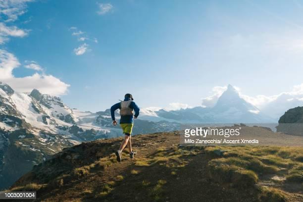 male trail runner ascends above glaciated landscape - top fotografías e imágenes de stock