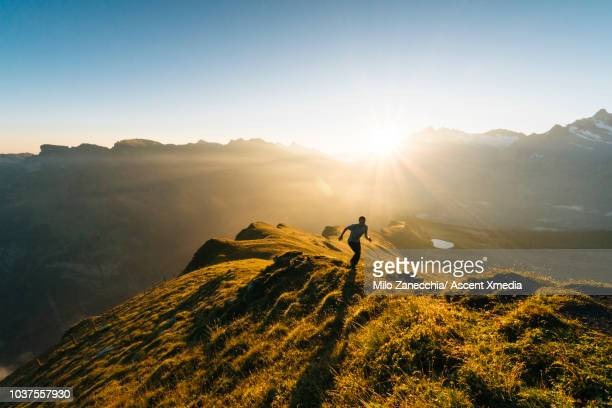male trail runner ascends mountain ridge, high above valley - cross country running stock pictures, royalty-free photos & images