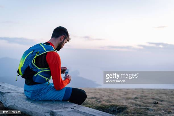 male trail runner enjoys granola bar - forward athlete stock pictures, royalty-free photos & images