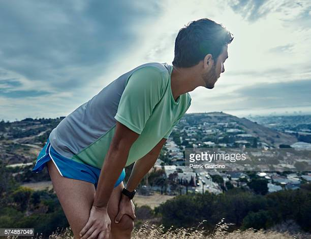 male trail runner - hand on knee stock pictures, royalty-free photos & images