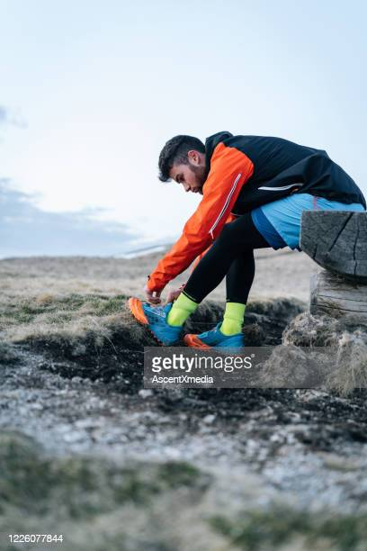 male trail runner ties up shoe laces before run - forward athlete stock pictures, royalty-free photos & images