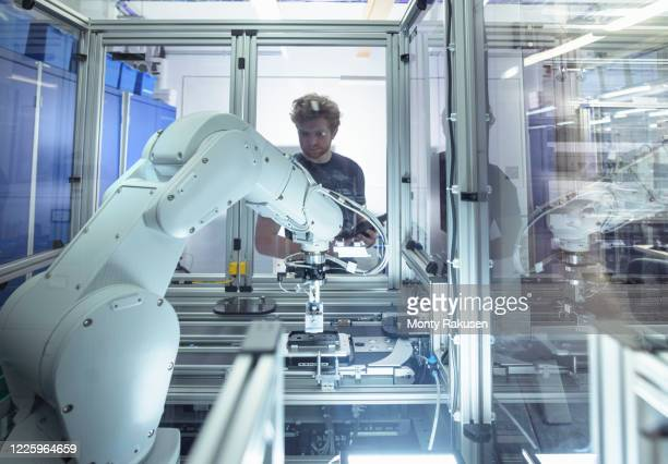 male trainee engineer with robotic equipment in unspecified. - ingénierie photos et images de collection