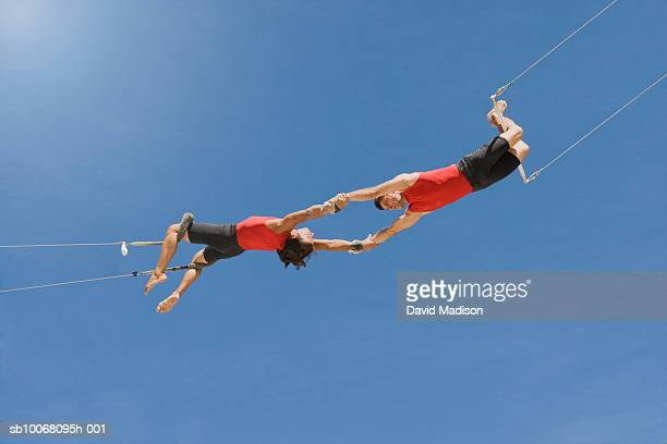 Male trapeze artist catching man, low angle view
