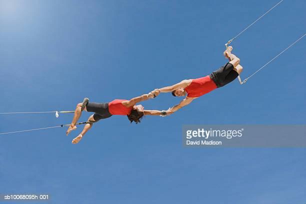 male trapeze artist catching man, low angle view - koordination stock-fotos und bilder