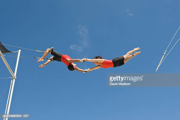 male trapeze artist catching woman, low angle view - trapeze artist stock photos and pictures