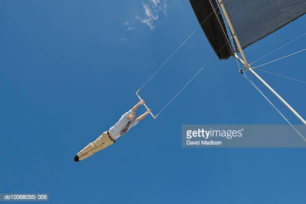 Male trapeze artist performing on trapeze, low angle view