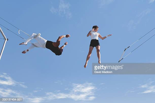male trapeze artist reaching to catch woman, low angle view - trapeze artist stock photos and pictures